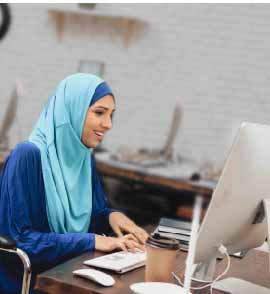 woman in hijab with physical disability working on her computer